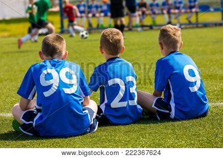 Children Soccer Team Watching Football Match. Children Sport Team in Blue Shirts. Youth Soccer School Tournament for Children. Young Boys in Soccer Jersey. Football Bench in the Background