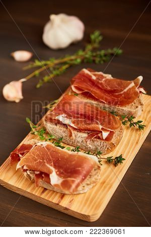 Sandwiches made from hand-made rye bread and thin chopped fresh bacon. Succulend bacon on a wooden board. Fresh green thyme.