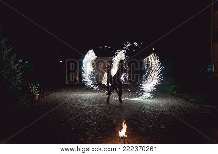 Fire dancing shows at night. Amazing fire show as part of wedding ceremony.