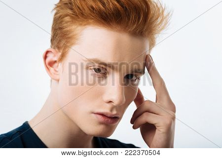 Red-headed. Handsome red-haired young man touching his forehead and having serious expression on his face and looking in the camera