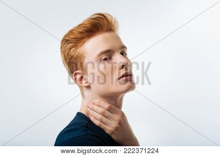 Stony-faced. Attractive unsmiling red-haired young man touching his neck and wearing a black T-shirt and looking in the camera