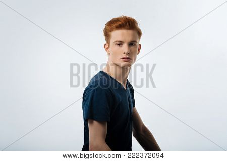 Model. Good-looking stony-faced red-haired young man having a modern hairstyle and wearing a black t-shirt and looking in the distance