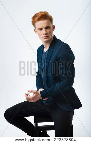 Meditation. Attractive serious red-haired young man wearing a black jacket and looking in the distance and touching his wrist