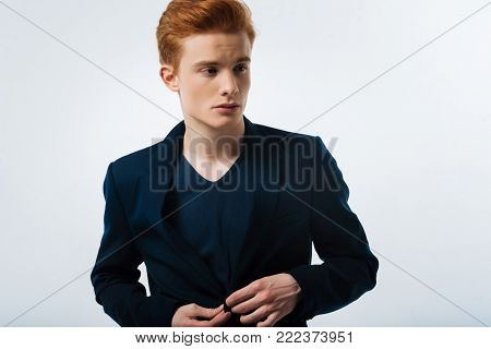 Stern. Good-looking earnest red-haired young man wearing a black jacket and buttoning it up and looking in the distance