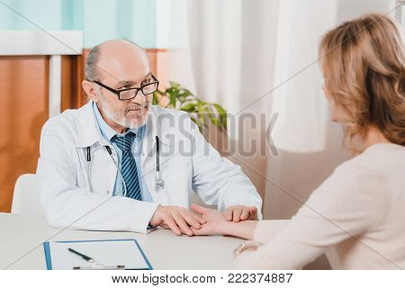 partial view of senior doctor checking patients pulse at workplace in clinic