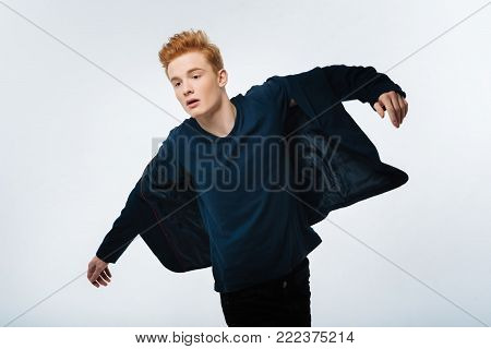 Cutie. Attractive earnest red-haired young man putting his jacket on and looking down and having a modern haircut