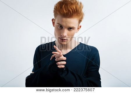 Cutie. Good-looking earnest red-haired young man taking off his jacket and staring and having a serious expression on his face