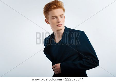 Thoughts. Attractive earnest young red-headed man buttoning up his jacket and having serious expression on his face and thinking