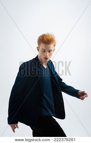 Red-haired. Handsome earnest young red-headed man wearing a jacket and looking down and walking