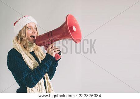Portrait of young women shouting using megaphone over background Girl in white shirt, studio shot .