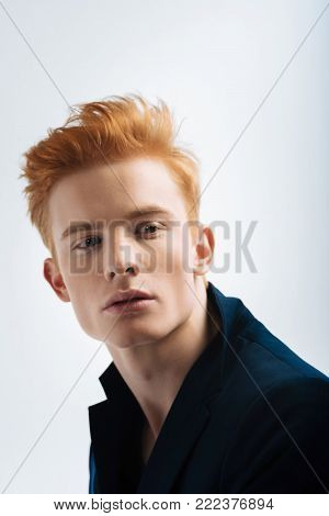 Red-haired. Attractive humourless red-headed young man wearing a black jacket and looking in the distance and thinking