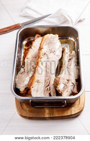 Roasted pork brisket in a frying pan. Grilled pork ribs.