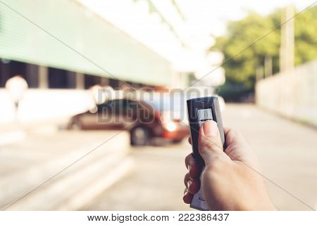 right hand hole remote car and press buttom to unlock door car with blur car park on background, vintage tone effect