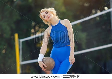 Young beautiful sporty girl outdoor in volleyball game. Attractive slim sexy woman standing with ball on the beach looking at camera. Summer holiday consept. Cute model in sport wear in sunny day