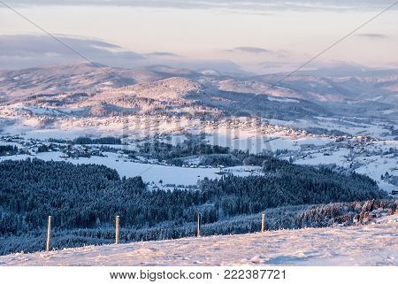 view from Ochodzita hill above Koniakow village in Silesian Beskids mountains in Poland with countryside, snow, frozen hills and blue sky with few clouds during freezing winter morning
