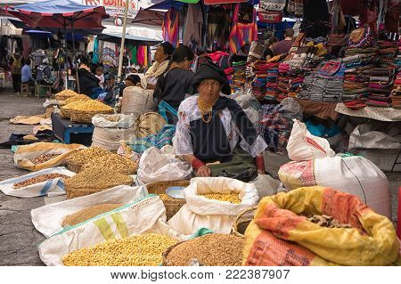 Otavalo, Ecuador - January 13, 2018: indigenous quechua woman selling produce from the ground in the Saturday farmer's market