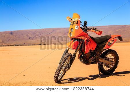 Merzouga, Morocco - February 22, 2016: A single orange motorbike sits alone on a flat stretch of sand in the Sahara desert under a blue sky with a large hill or mountain in the distance