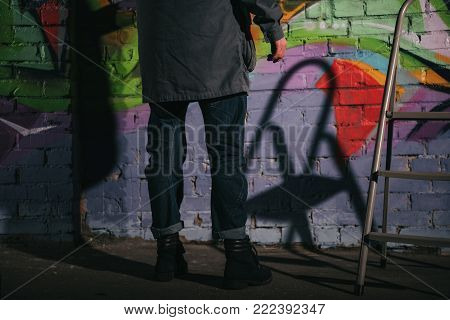 low section of street artist painting graffiti on wall at night