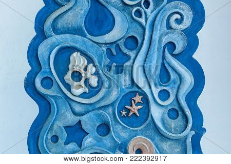 Gypsum decorative ornament of blue color with marine inhabitants on a white wall.the sea and the fish on the wall