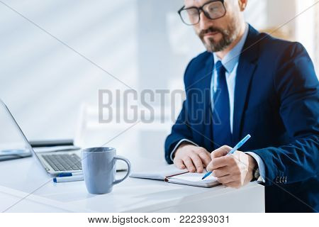 Accurate timing. Serious skillful bearded man writing down thoughts while wearing glasses and staring down