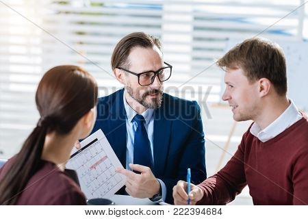 Team brainstorm. Focused young three colleagues gathering for meeting while man wearing glasses and pointing at the document