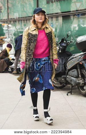 MILAN, ITALY - JANUARY 15: Fashionable woman poses outside Armani fashion show during Milan Men's Fashion Week on JANUARY 15, 2018 in Milan.