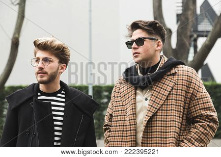 MILAN, ITALY - JANUARY 15: Fashionable people pose outside Armani fashion show during Milan Men's Fashion Week on JANUARY 15, 2018 in Milan.