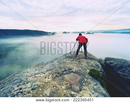 Photo artist in work. Photographer in rocky mountains. Traveller takes photos of dreamy majestic landscape, sunset at horizon
