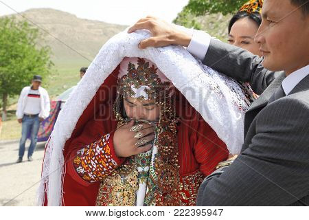 Kov-Ata, Turkmenistan - April 30, 2017: Turkmen national wedding in the village of Kov-Ata. The groom shows his bride's face to the guests.  Turkmenistan - April 30, 2017.