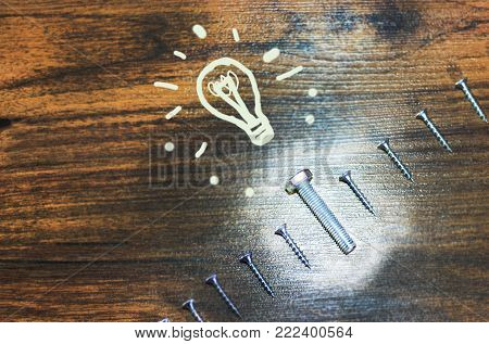 The concept of business is minimal, like a group of screws on a wooden background and a bolt is not like the rest. A painted light bulb, there are people not like everyone else, and their potential is not known.