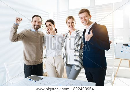 Go home. Budding appealing four colleagues staring at the camera while standing near the table and laughing