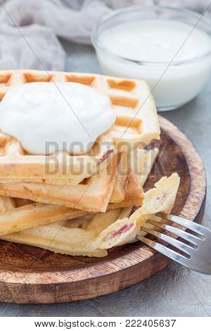 Homemade savory belgian waffles with bacon and shredded cheese, served with plain yogurt on a wooden plate, vertical