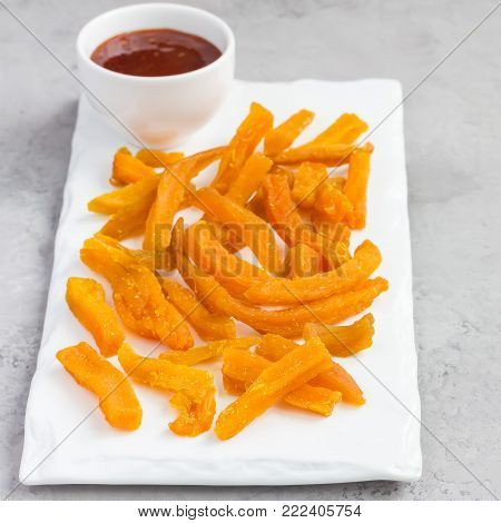 Healthy baked sweet potato fries on white plate served with spicy sauce, square