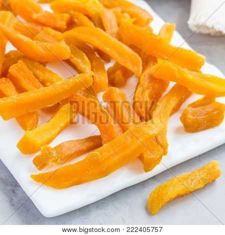 Healthy baked sweet potato fries on white plate served with spicy sauce, square format