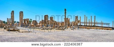 PERSEPOLIS, IRAN - OCTOBER 13, 2017: Panorama Persepolis archaeological complex, the ruins of Hundred Columns Hall are neighboring with slender columns of Apadana palace, on October 13 in Persepolis.