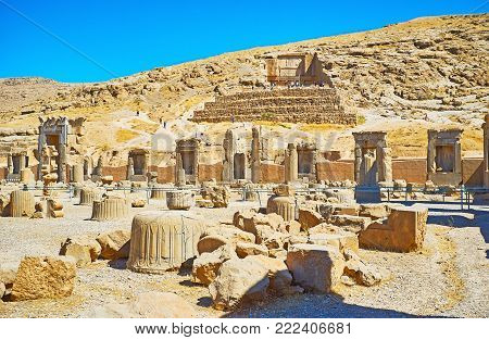 Discover Persepolis archaeological site with its ancient landmarks - tomb on the mountain slope and Hundred Columns hall, located at the foot of Rahmet Mount, Iran.