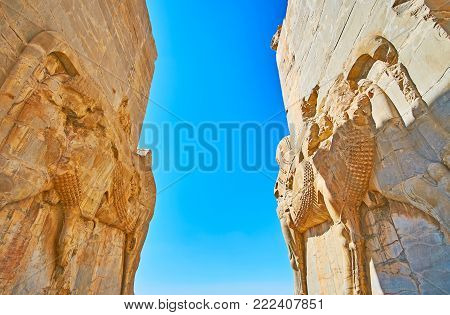 The ancient giant statues of bulls on walls of All Nations (Xerxes) Gate in Persepolis archaeological site, Iran.
