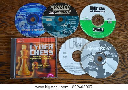 WREXHAM, UK - FEBRUARY 20, 2014: A random collection of early CD-ROM software games and programmes on a wooden table.