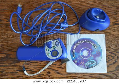 WREXHAM, UK - FEBRUARY 20, 2014: Unpackaged Digital Blue movie creator. Childrens movie camera with docking station and CD-ROM software on a wooden table.