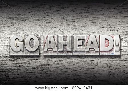 go ahead exclamation made from metallic letterpress on rough wooden texture
