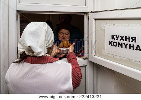 Berehove, Ukraine - December 14, 2017: A poor woman receives a hot lunch in a public kitchen for poor and homeless people.