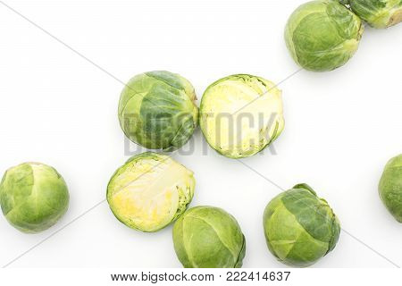Raw Brussels sprout heads and two halves top view isolated on white background