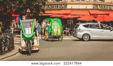 PARIS, FRANCE - July 11, 2017 : bicycle taxis drivers wait for customers in front of the terrace of a restaurant on a summer day