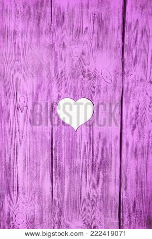 White heart carved in a wooden pink board. Background