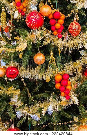 Close up of a christmas tree decorated with golden tinsel and gold tinged orbs
