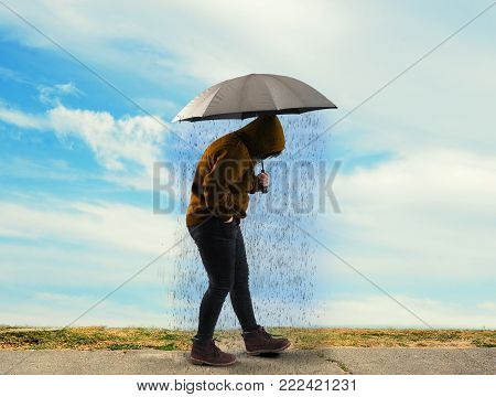 Woman holding an umbrella and raining on a sunny day. Concept of depression.