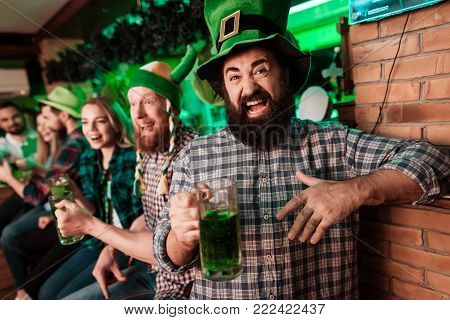 The guy in the cap of the leprechaun is drinking beer. They are celebrating St. Patrick's Day with friends. They have fun at the bar.