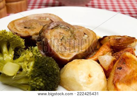 Breast of welsh lamb A whole cooked breast of Welsh lamb rolled and stuffed on a bed of vegetables