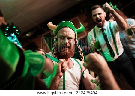 Two men fight in a bar. He celebrated St. Patrick's Day with friends.