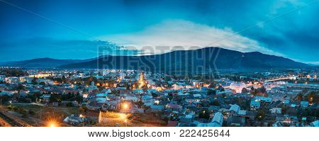 Gori, Shida Kartli Region, Georgia. Panoramic Cityscape In Bright Yellow Evening Illumination Under Blue Sky In Autumn Twilight.  Aerial View Of City. Travel Destination In Night Illuminations Lights.